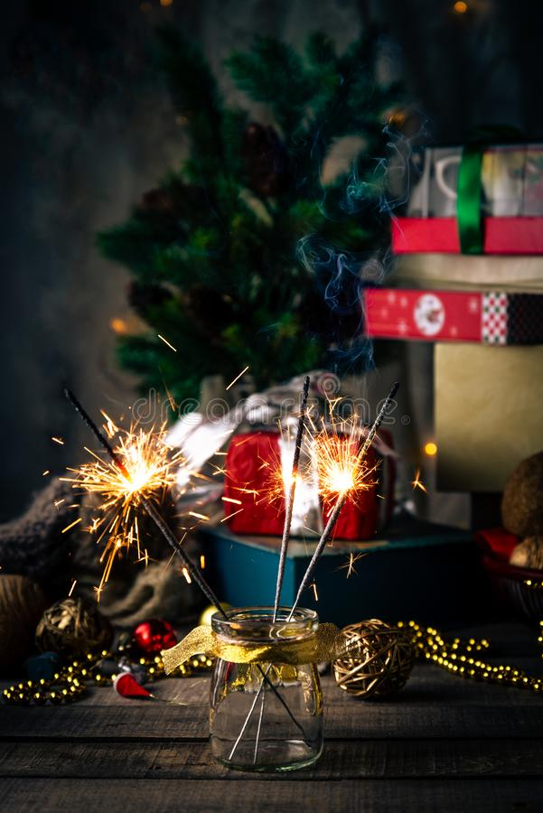 Sparkling bengal lights, Christmas tree, decorations, gift boxes on a wooden rustic background stock image