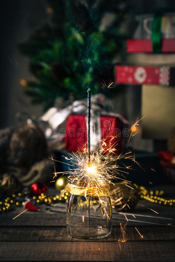 Sparkling bengal lights, Christmas tree, decorations on a wooden rustic background stock photo
