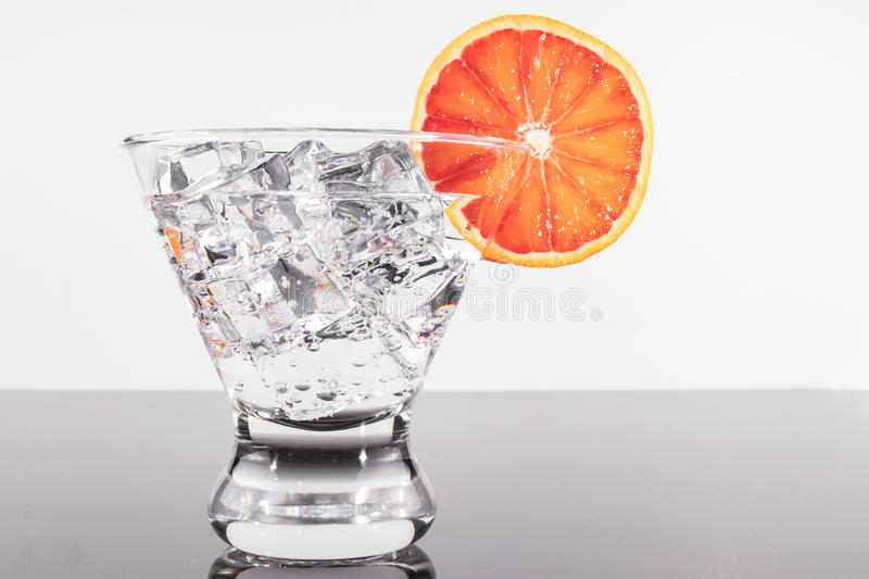 Sparkling beverage in a martini glass with blood orange slice royalty free stock photo