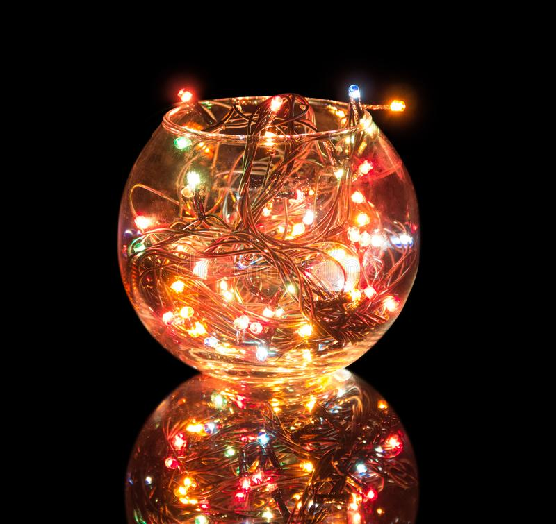 Sparkling Christmas garland is located in round glass shape isolated on black. Background stock photo