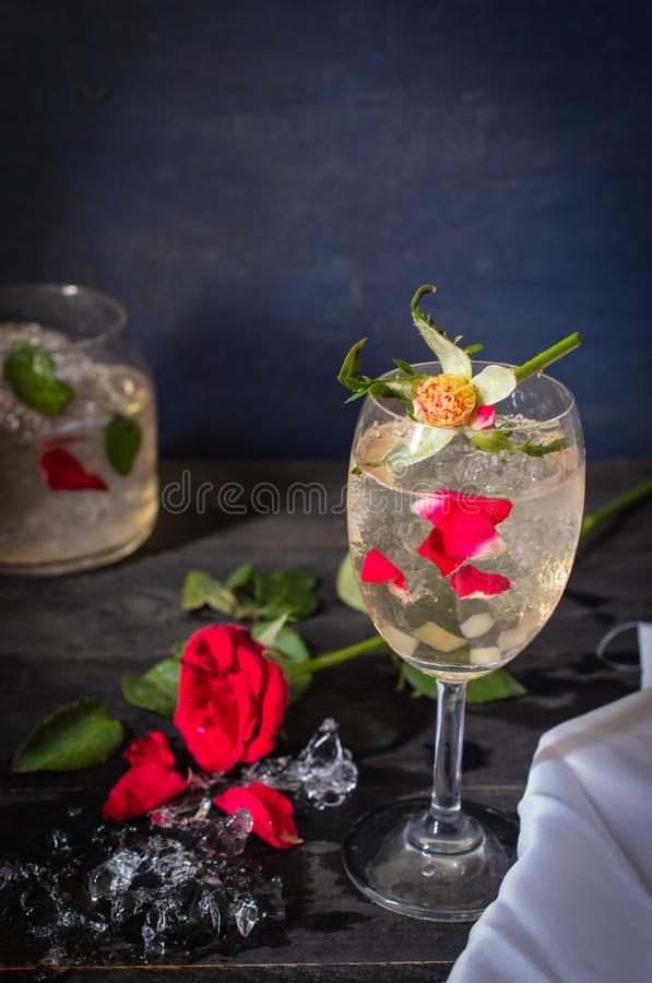 Sparkling cold water detox with rose and ice on the wood table there are rose, diferance glass and ice placed around. Close up royalty free stock photo