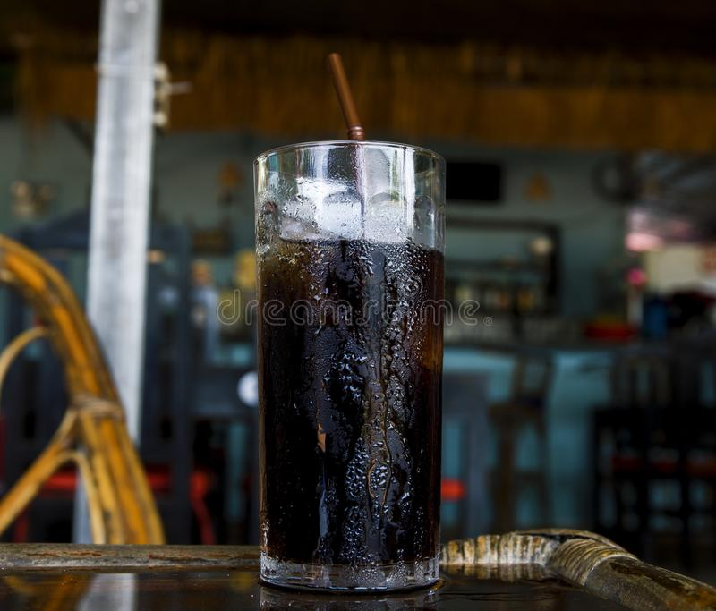 Sparkling drink with ice in glass. Cool beverage in hot summer day. Coke in glass with straw royalty free stock photo