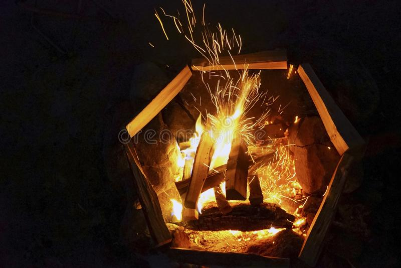 Sparkling fire in the fire with wood at night on a black background. royalty free stock photo