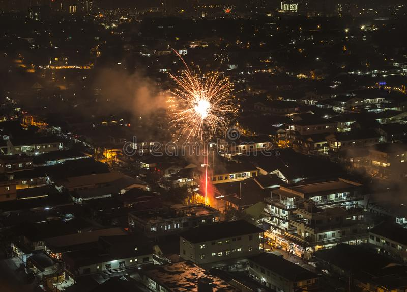 Sparkling firework bursting above Asian neighbourhood royalty free stock photos