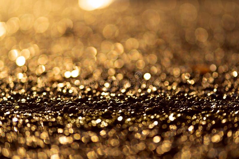 Sparkling light boke blur. Golden glitter particles background. Sparkling light boke blur. Sea pebbles. Golden glitter particles background royalty free stock image