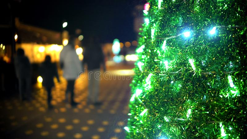 Sparkling lights on Christmas tree, family with children strolling on background. Stock footage stock image