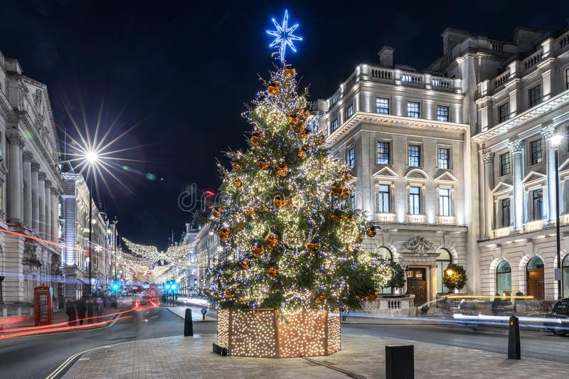 A sparkling, lit christmas tree in the center of London, United Kingdom. During winter might time with blurred street traffic royalty free stock images