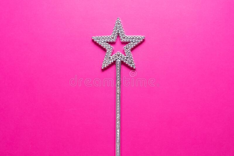 Sparkling magic wand on a pink background. Concept of celebration and magic, copy space. stock image