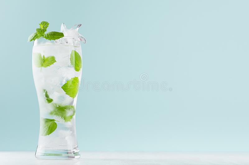 Sparkling organic water with mint green leaves, ice cubes, sparkling water in misted glass in modern mint color interior. royalty free stock photography