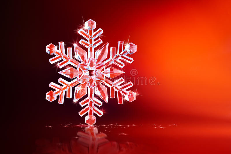 Sparkling snowflake. Sparkling christmas decoration over red background stock photography