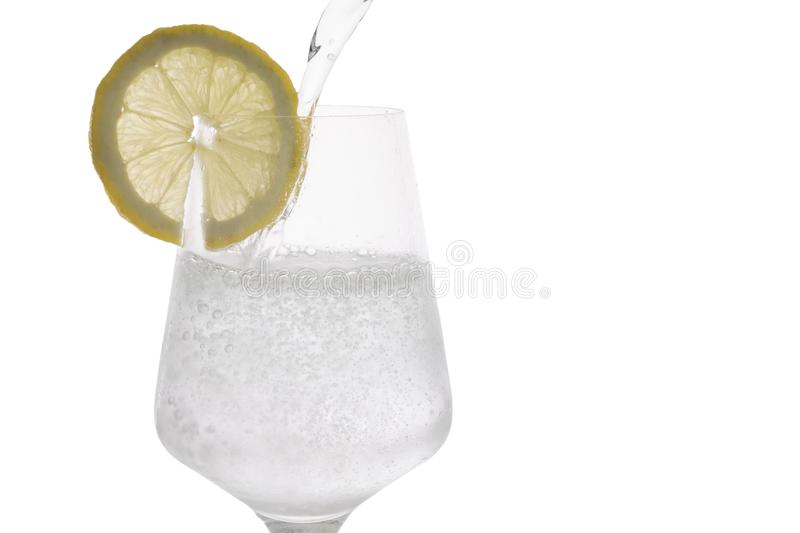 Sparkling water being poured into a glass with a slice of lemon stock photography