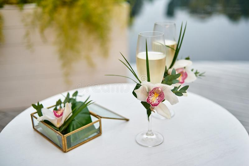 Sparkling wedding glasses with champagne, orchid flower decor and wedding rings in box in blur on white table outdoors, copy space royalty free stock photography
