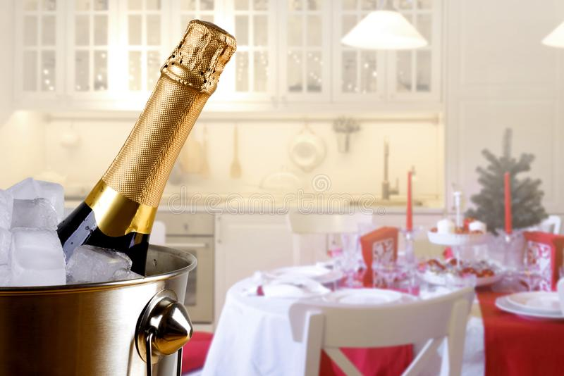 Sparkling wine bottle in ice bucket on festive kitchen background royalty free stock images