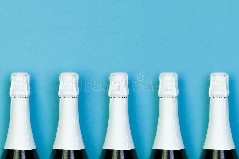 Sparkling wine bottle in row on blue background. Holidays, party and celebrations concept royalty free stock photography