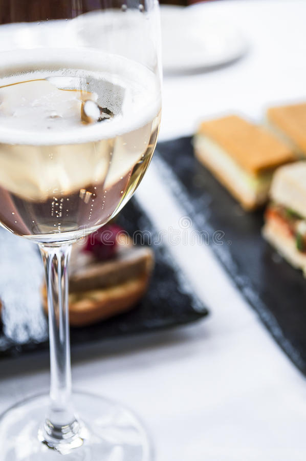 Sparkling Wine with Traditional Afternoon High Tea. Close up of sparkling wine in glass with traditional afternoon high tea desserts in the background royalty free stock photo