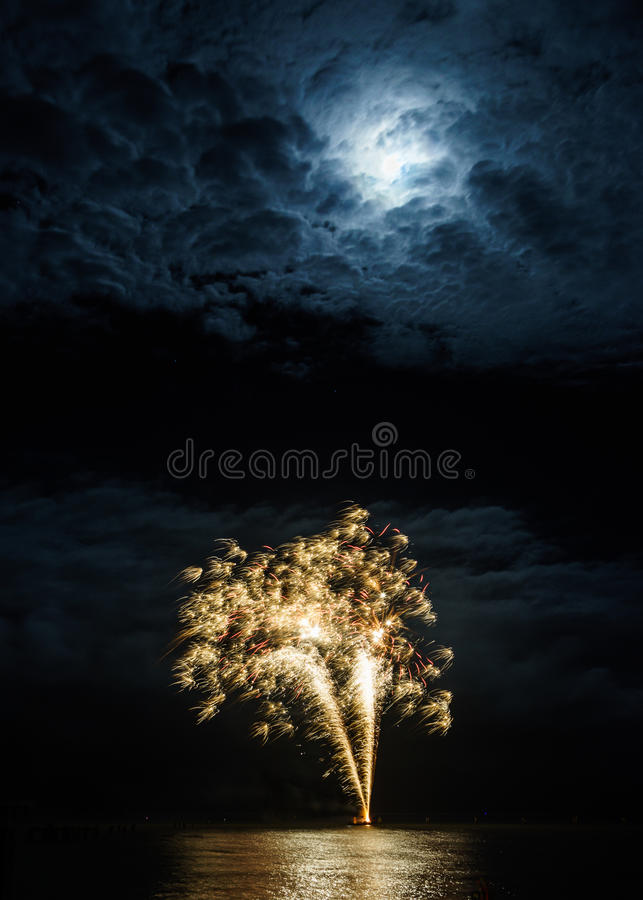 Sparkly fireworks under the moon royalty free stock image