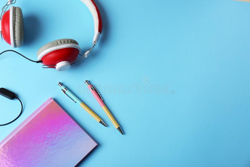 Sparkly notebook, pens and headphones on color background, flat lay. Space for text stock photo
