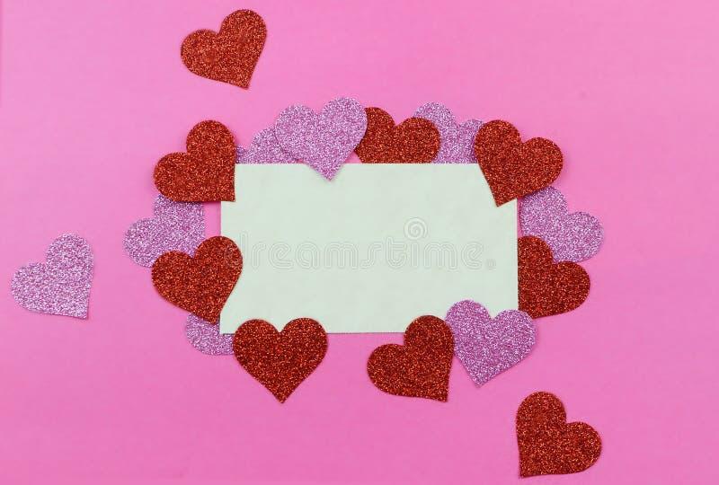 Sparkly Rosa und rote Herzen umgeben ein Pergamentpapier tage auf einem hellen rosa Hintergrund für Valentinstag im Februar Kopie stockfotografie