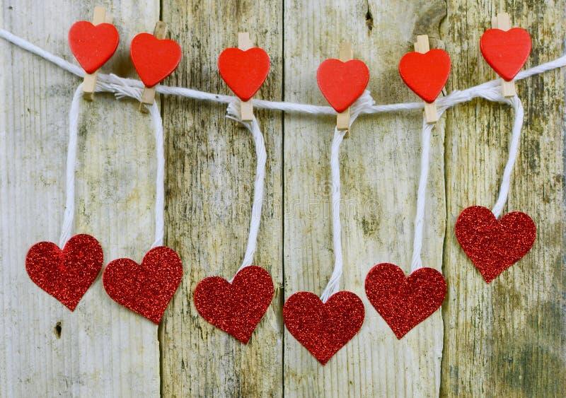 Sparkly rote Herzen, die von verzierten Wäscheklammern durch Schnur vor rustikalem hölzernem Hintergrund für Valentinstag übergeb lizenzfreie stockbilder