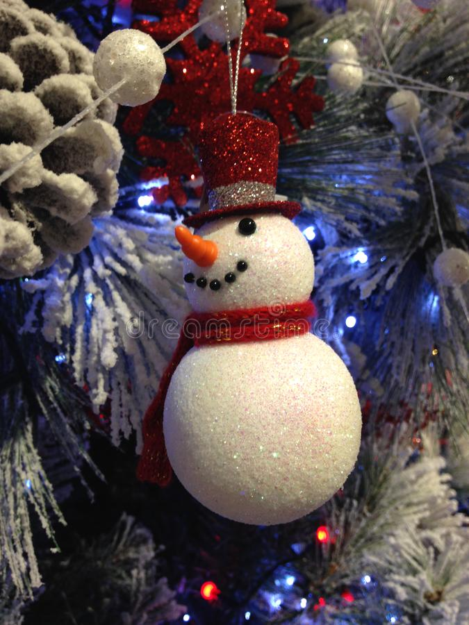 Sparkly snowman hanging on a white Christmas tree stock image