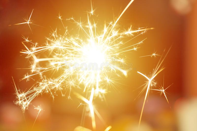 Sparks from hand cold fireworks bright sunspot background stock image