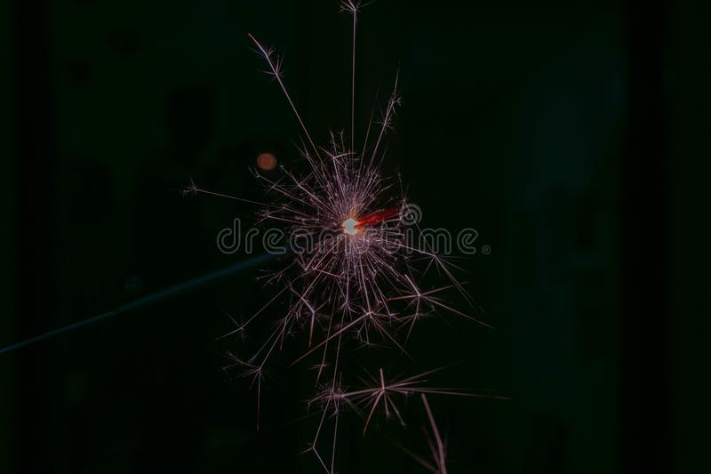 Sparks from a lit sparkler on a dark background. Bright sparks from a lit sparkler on a dark background royalty free stock photo