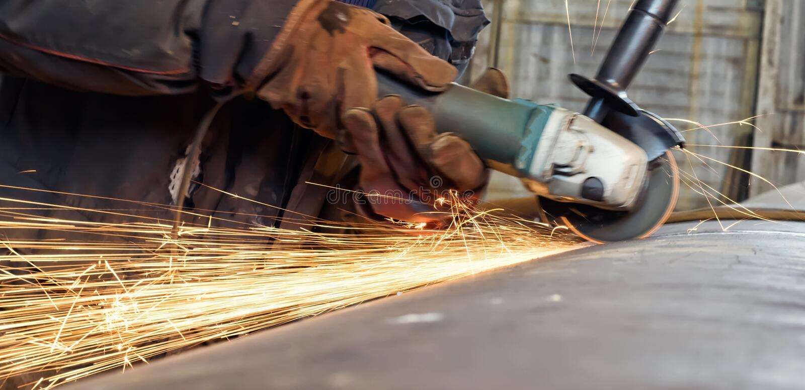 Sparks when machining a weld bead on the pipe. Mechanized cleaning of the root surface of the weld control sample of thick-walled stainless steel pipe stock photography