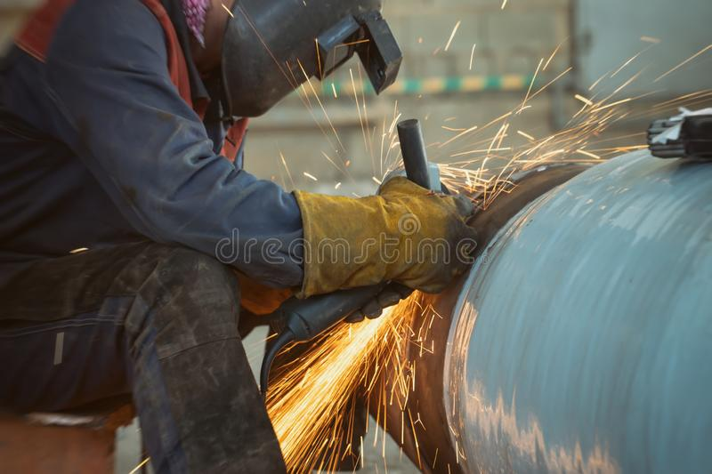 sparks from Stripping machine in processing of root weld in welding of pipeline elements stock photography