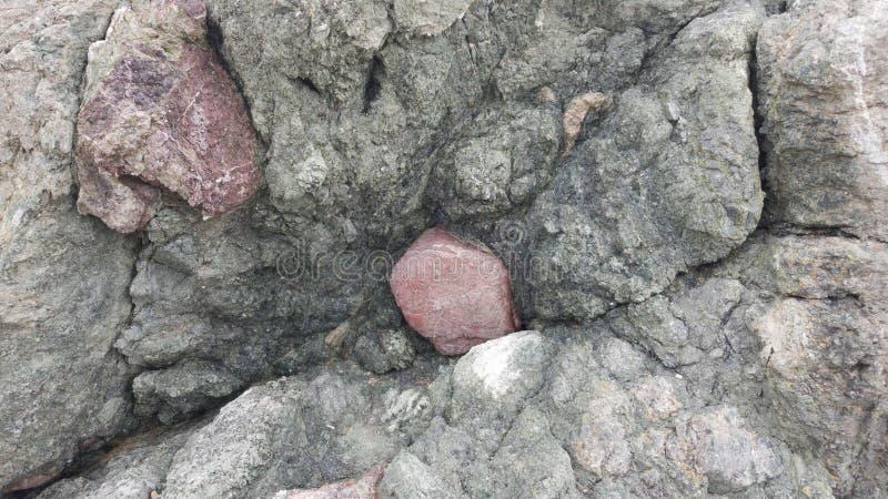 Sparpagliato con le grandi pietre rosse in una roccia verdastra fotografie stock