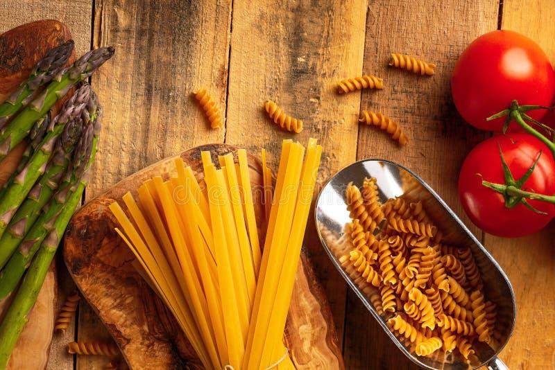 Sparris, och kronärtskockan och kvisten av tomater och söt röd italiensk spagetti för peppar och på en skärbräda med en kniv, fotografering för bildbyråer