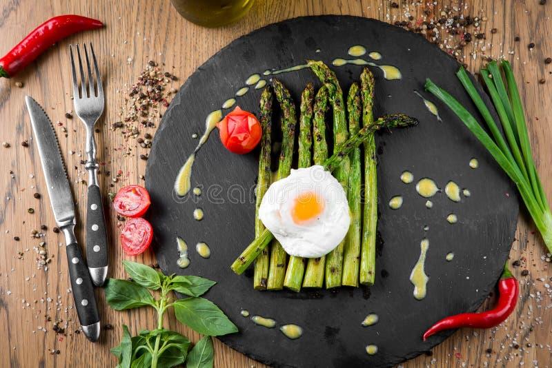 Sparris som lagas mat på ett galler med den stekte äggsås och tomaten royaltyfri fotografi