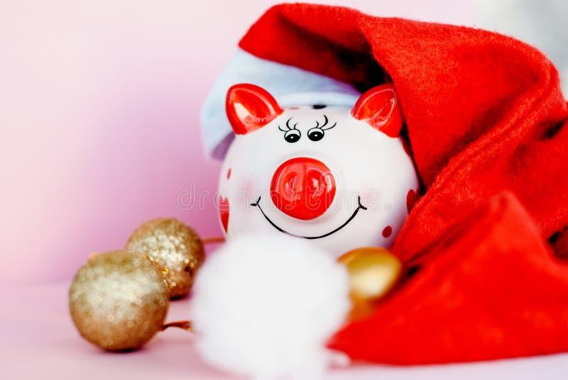 Sparschwein über rosa Hintergrund mit Weihnachtsdekorations-Kopienraum Jahr von Schwein 2019 stockbild