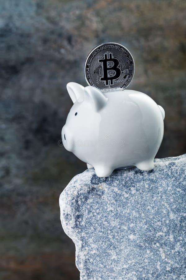Sparschwein mit bitcoin auf Steinklippe stockbilder