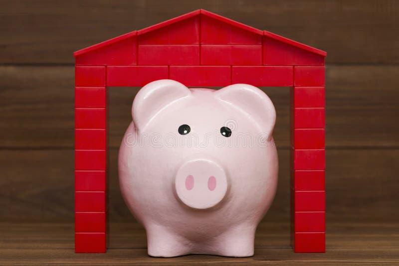 Sparschwein mit Dach auf hölzernem Hintergrund stockfoto