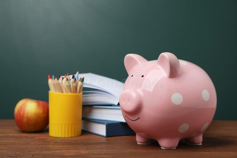 Sparschwein mit Stapel von Büchern und von Apfel lizenzfreies stockbild