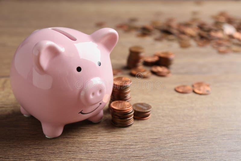 Sparschwein und M?nzen auf Holztisch Banknoten mit schwarzem Rechner stockbild
