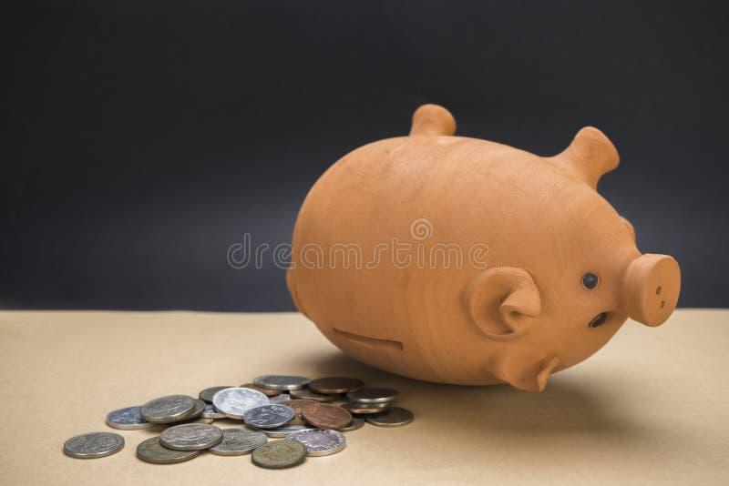 Sparschwein von Keramik entleert nahe bei einigen Münzen lizenzfreie stockfotografie