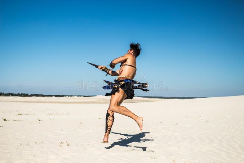 Spartaans draait dynamisch in een sprong met een zwaard royalty-vrije stock afbeeldingen