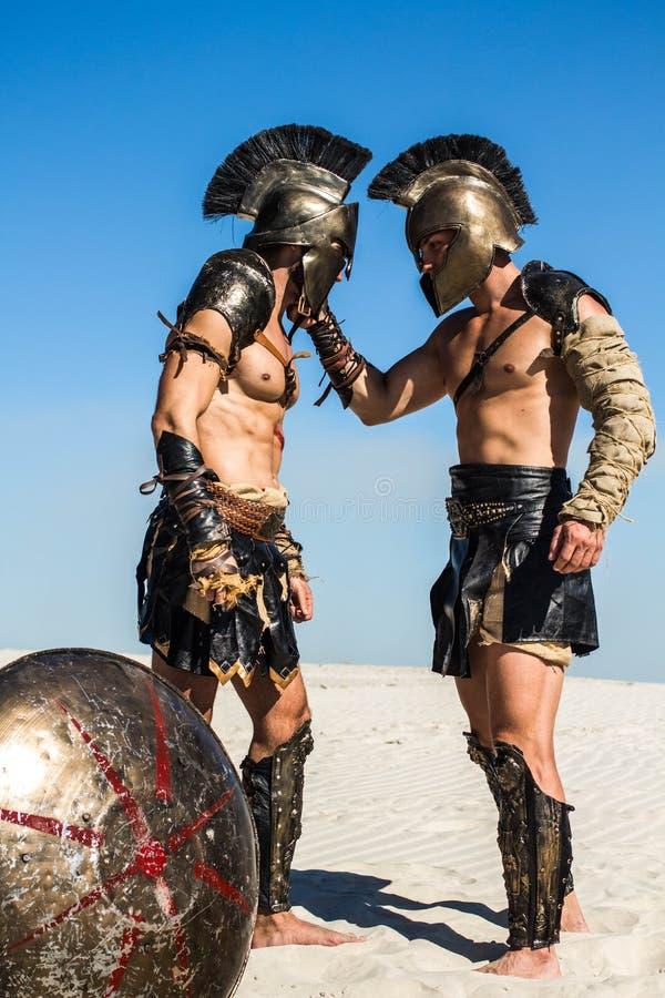Spartaanse strijder die een Romein voor zijn helm houden royalty-vrije stock fotografie