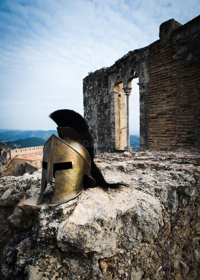 Spartan helmet on castle ruins royalty free stock photos