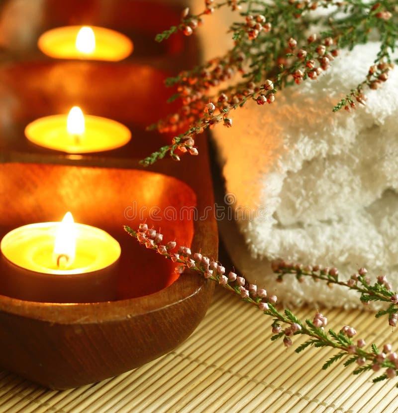 Spasammansättning av handduken, stearinljus och blommor. arkivbild