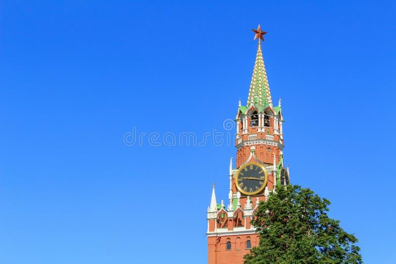 Spasskaya-Turm von Moskau der Kreml auf einem grünen Baumhintergrund gegen blauen Himmel am sonnigen Sommermorgen lizenzfreie stockfotos