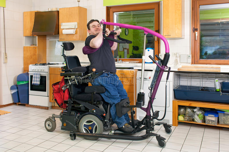 Spastic young man using a patient lift. stock image