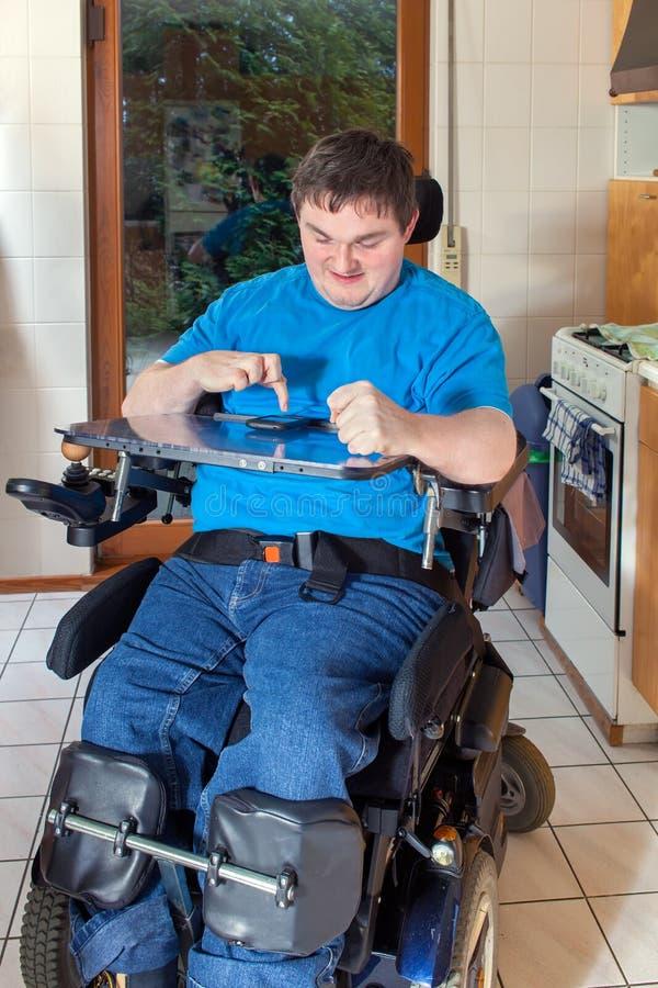 Spastischer junger Mann begrenzt auf einem Rollstuhl lizenzfreies stockfoto