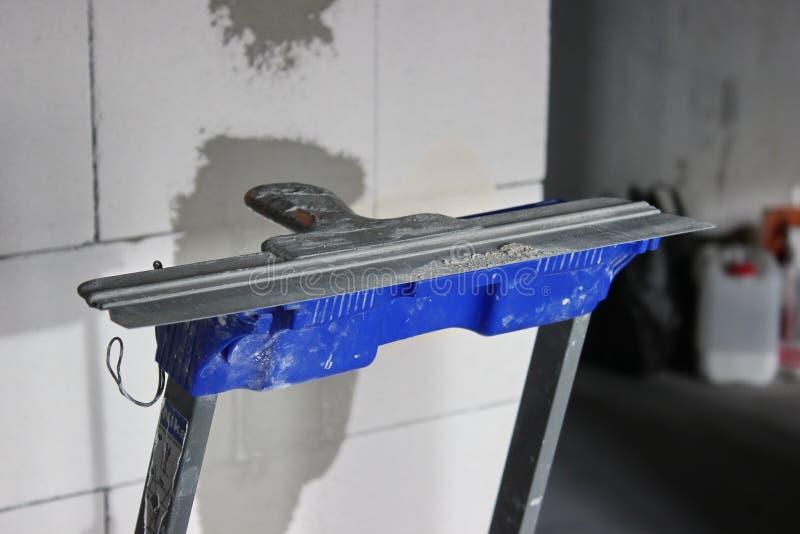 Spatel tegen de muur van gelucht beton reparatie in de flat of het huis, bouwmaterialen, bouwwerkzaamheid stock afbeelding