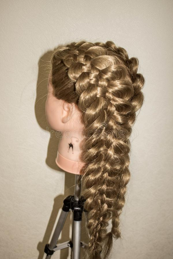 Spatial braids of 5 strands. On the training mannequin with hair stock photo