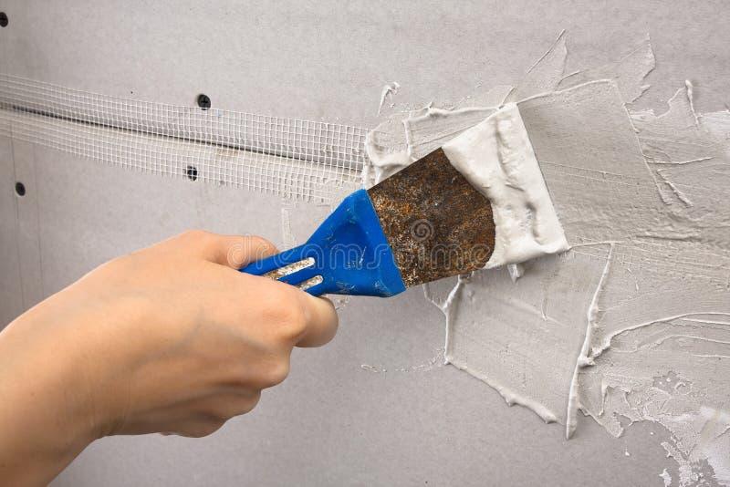 Spatule avec le plâtre à disposition pendant le plâtrage des murs, plan rapproché image libre de droits