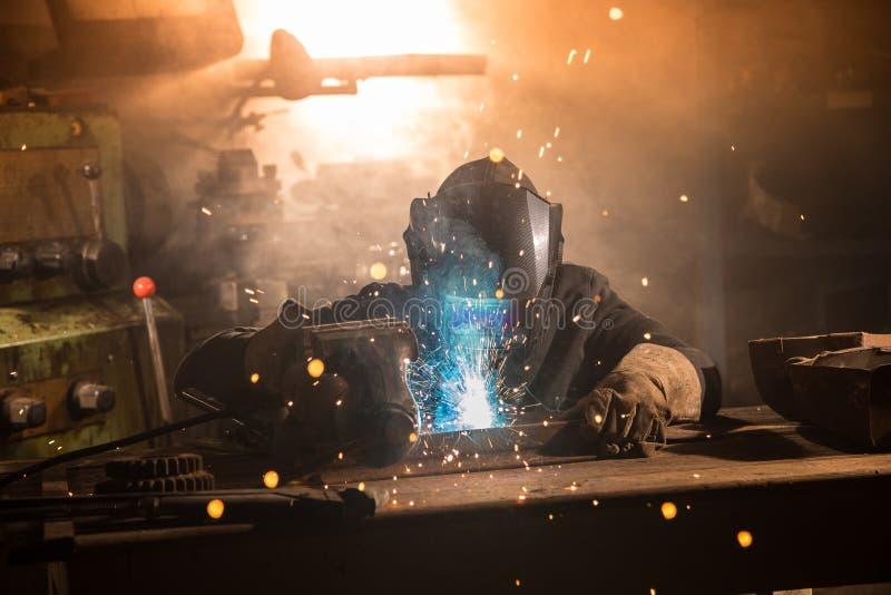 Spawacz jest spawalniczym metalu częścią w fabryce zdjęcia royalty free
