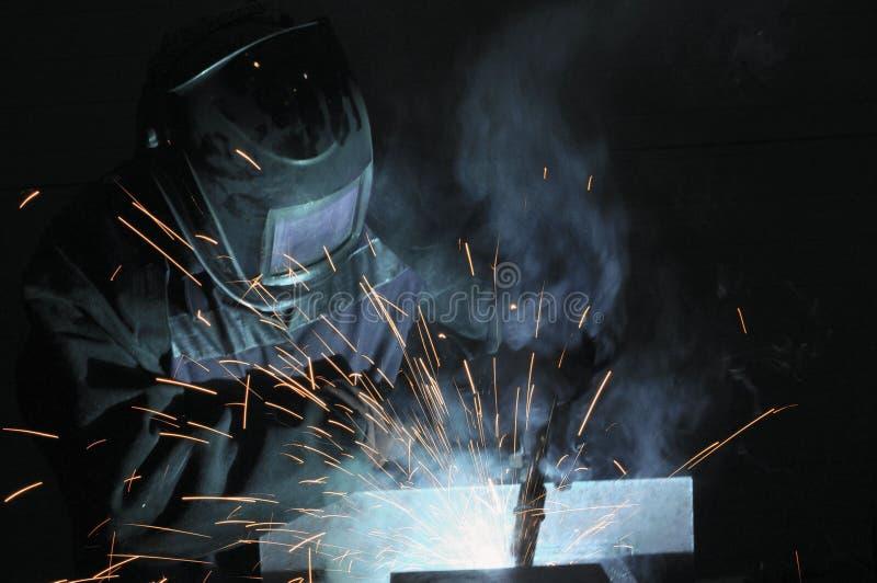 Spawacz na produkcji spawka metal Iskry latają, dymią, zdjęcia stock