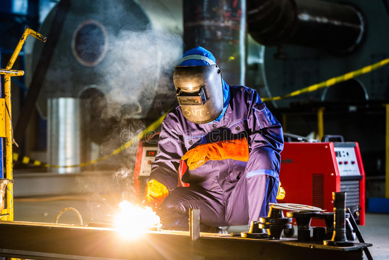 Spawacz pracuje w przemysłowej fabryce obrazy stock